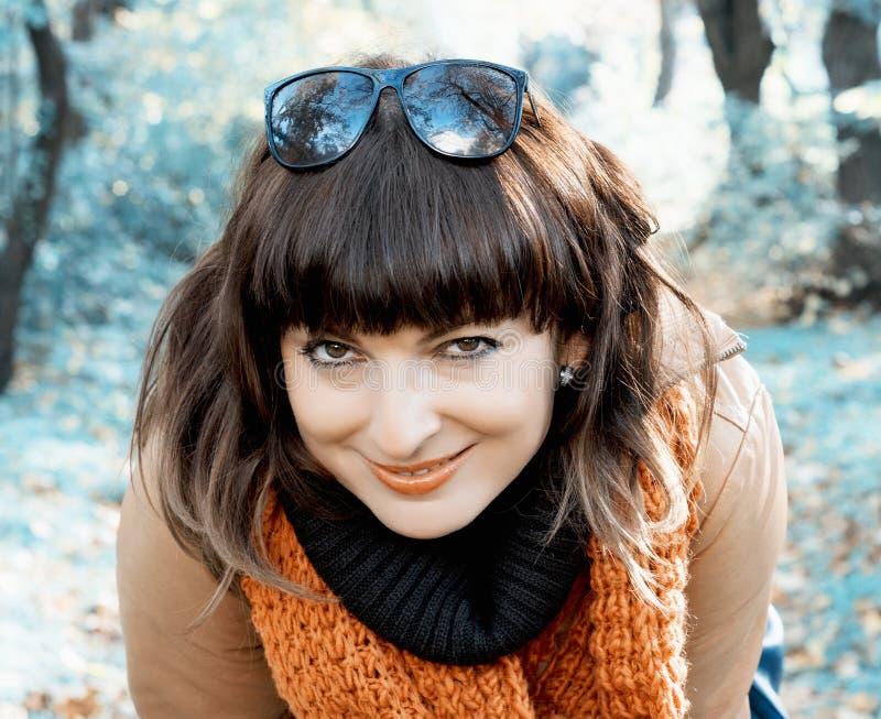 摆在秋天公园的微笑的妇女 库存照片