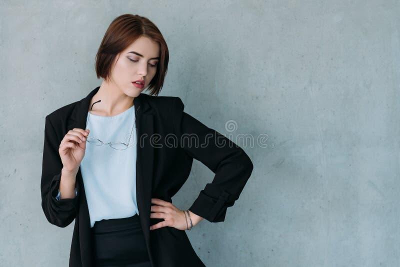 摆在眼睛的年轻可爱的企业夫人下来 免版税库存图片