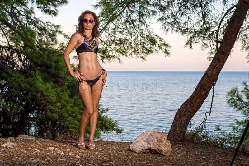 摆在的泳装的性感的年轻女人户外 免版税库存图片