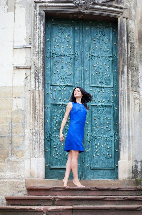 摆在照相机的一件蓝色礼服的少女在绿色金属门背景  确信的时髦的妇女看对边 免版税库存图片