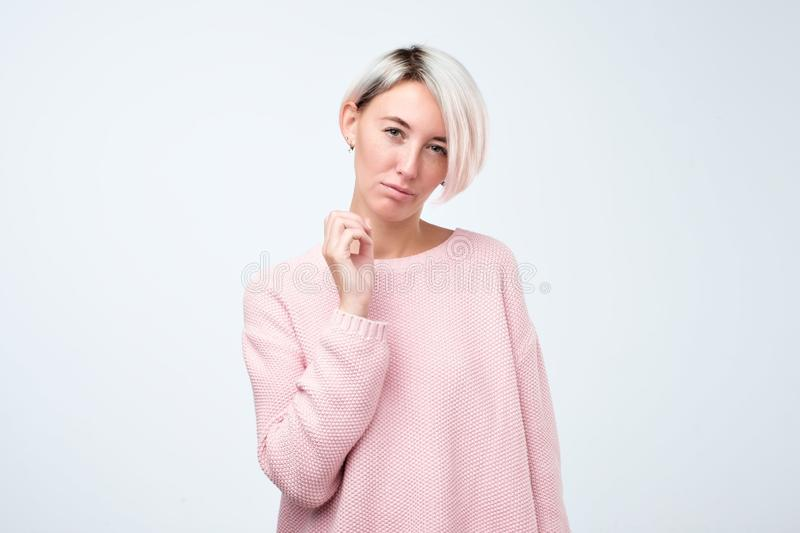 摆在用横渡的手的桃红色毛线衣的严肃的行家女孩 免版税库存图片