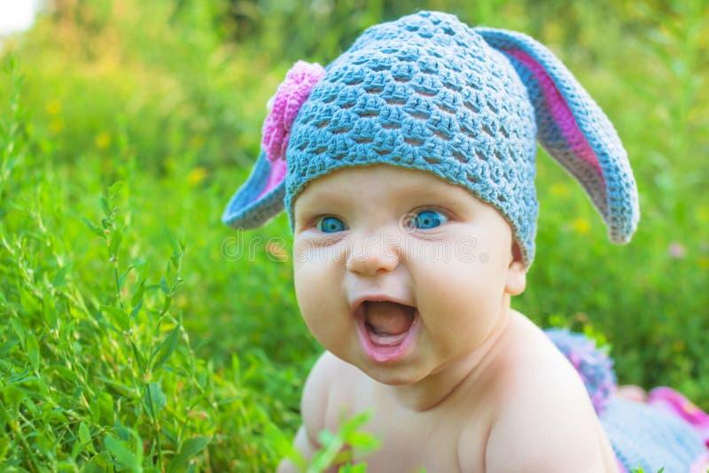 摆在象复活节兔子的微笑的婴孩孩子 儿童乐趣有 免版税库存照片