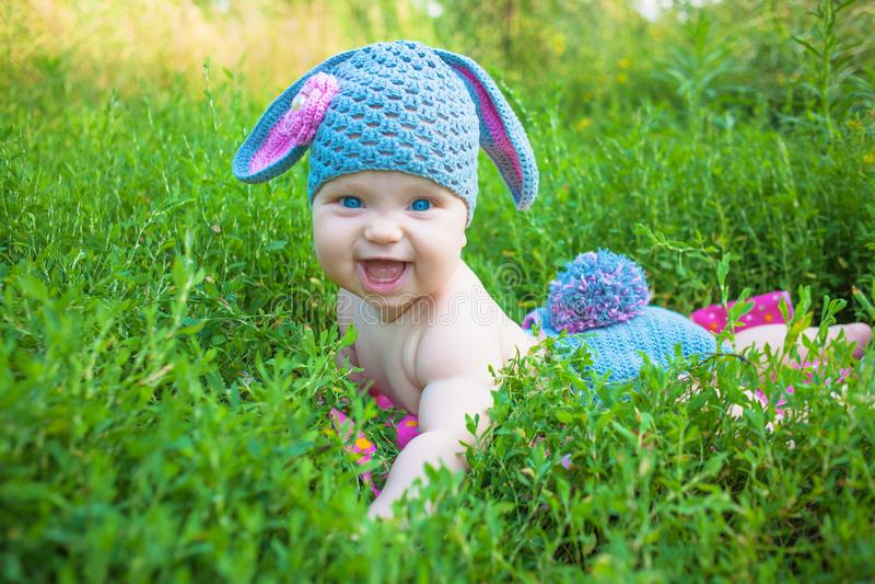 摆在象复活节兔子的微笑的婴孩孩子 愉快的子项 库存图片