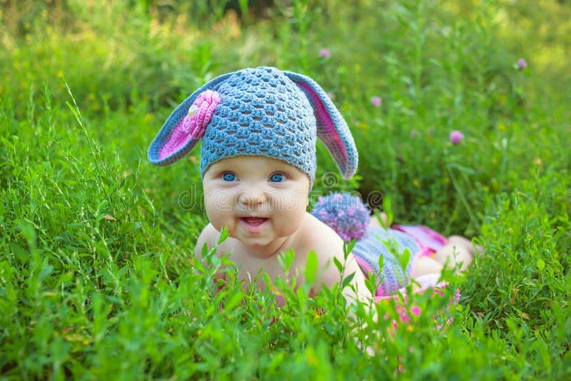 摆在象复活节兔子的微笑的婴孩孩子 免版税库存图片