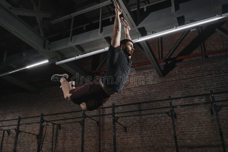 摇摆在体操圆环的年轻crossfit运动员做引体向上在健身房 锻炼锻炼 库存图片