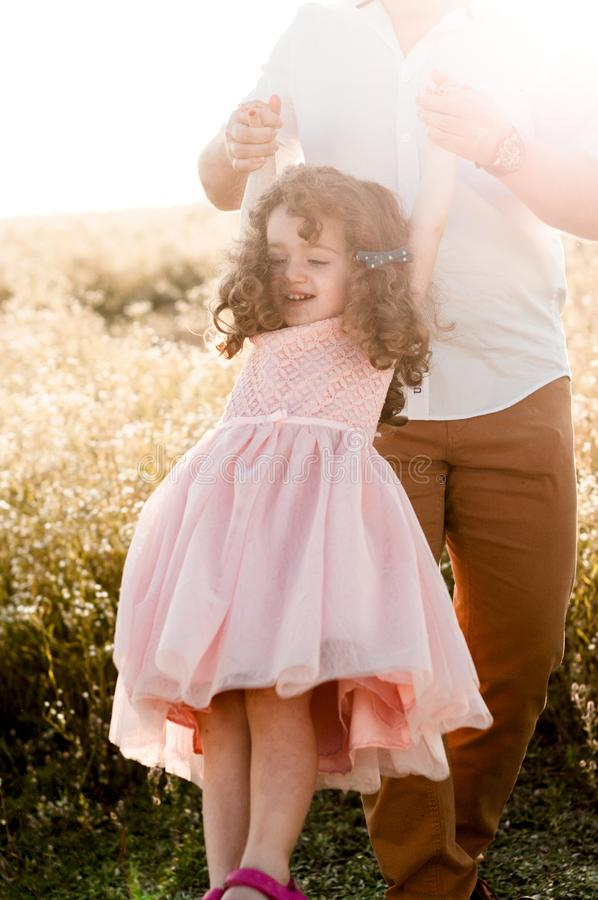 摇摆有卷发的父亲一女孩在桃红色礼服 库存照片