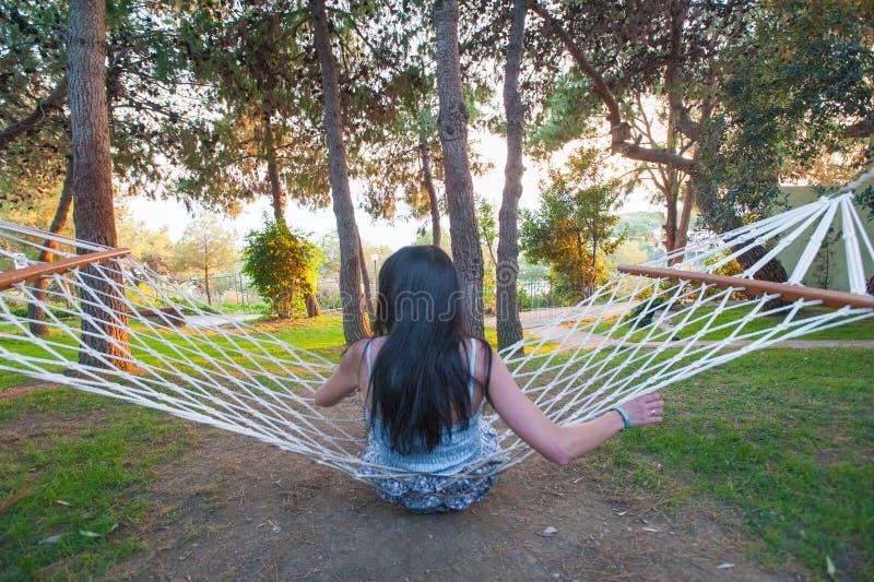 摇摆的吊床的女孩,当敬佩绿色自然时 库存照片