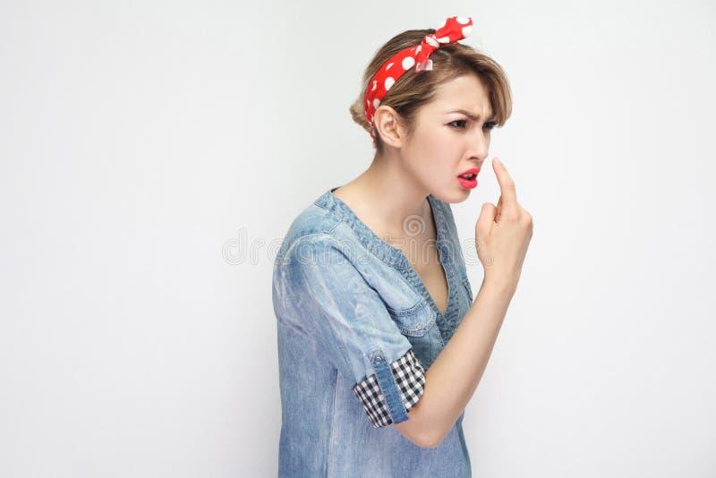 您是说谎者 恼怒的美丽的年轻女人画象偶然蓝色牛仔布衬衣的有构成和红色头饰带身分的与谎言 免版税库存照片
