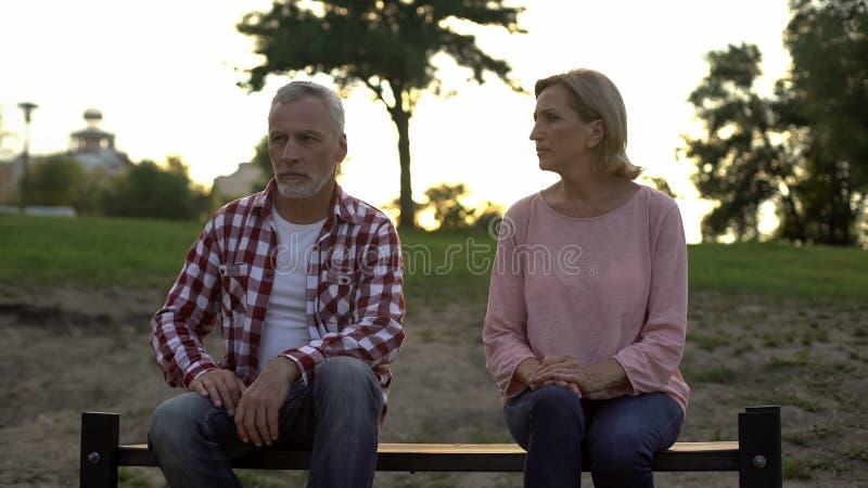 悲哀资深夫妇坐长凳,看沮丧的丈夫的妻子 免版税库存照片