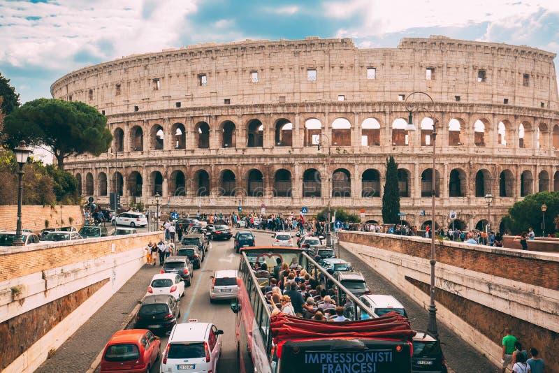 意大利罗马 罗马斗兽场 在蛇麻草的红色蛇麻草观光的旅游公共汽车在Flavian圆形露天剧场附近的街道 著名 库存照片