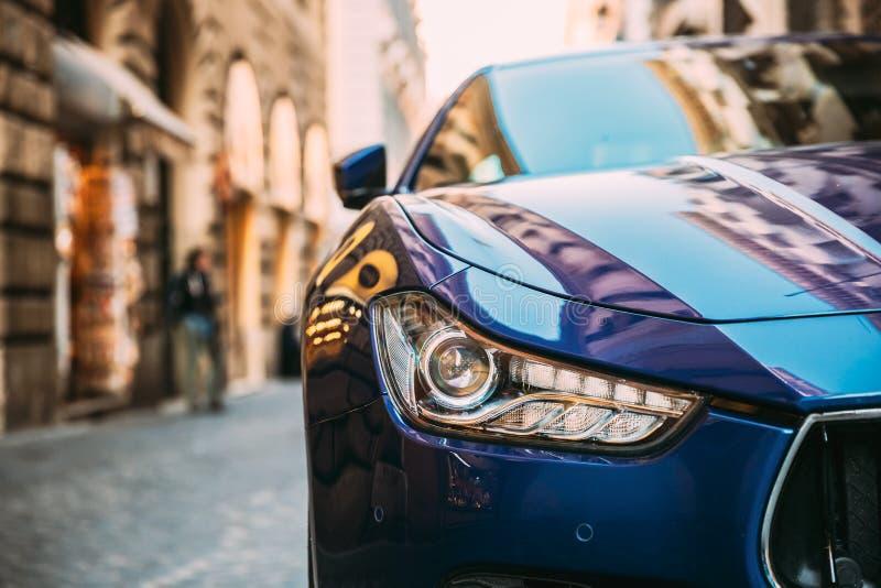 意大利罗马 蓝色玛莎拉蒂吉卜力M157接近的车灯停车场在街道 库存照片