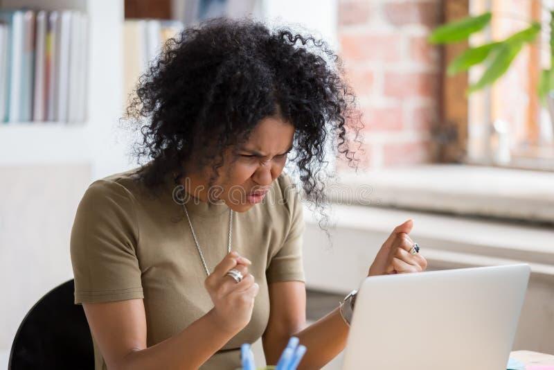 感觉疯狂的愤怒的怨恨的恼怒的疯狂的非洲女实业家黏附了膝上型计算机 免版税库存图片