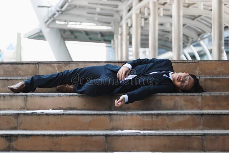 感觉疲倦的和失望的年轻亚裔的商人躺下和注重 失业和临时解雇概念 图库摄影