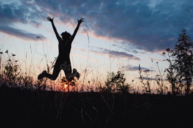 愉快地跳在日落光的女孩 夏天,自然,室外,自由,成功,幸福概念 免版税库存照片