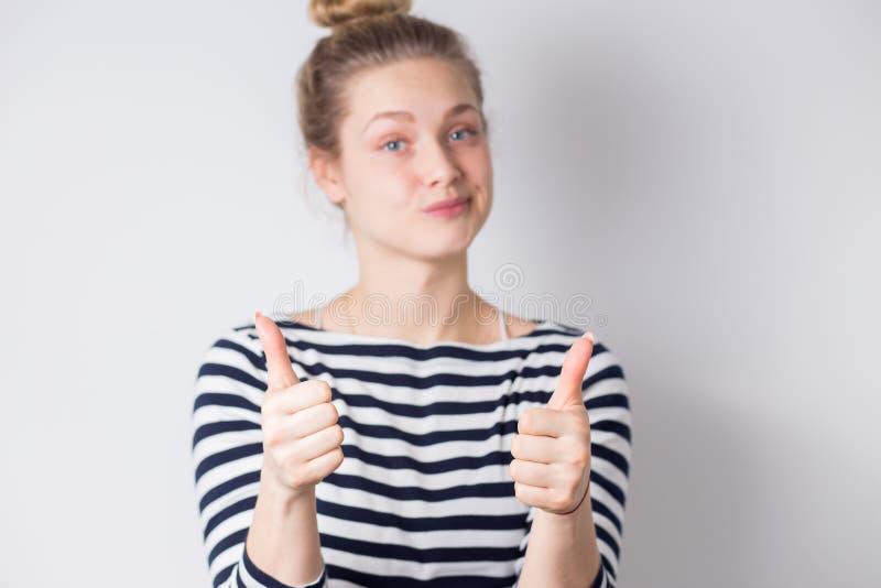 愉快和成功的年轻女商人显示赞许用两手和微笑在白色背景 正面情感,面部 免版税库存图片