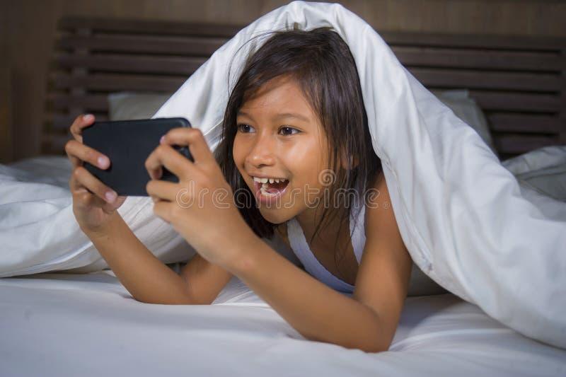 愉快和美好的7岁获得的儿童打与手机的乐趣互联网比赛说谎在快乐和激动的床上  免版税库存照片