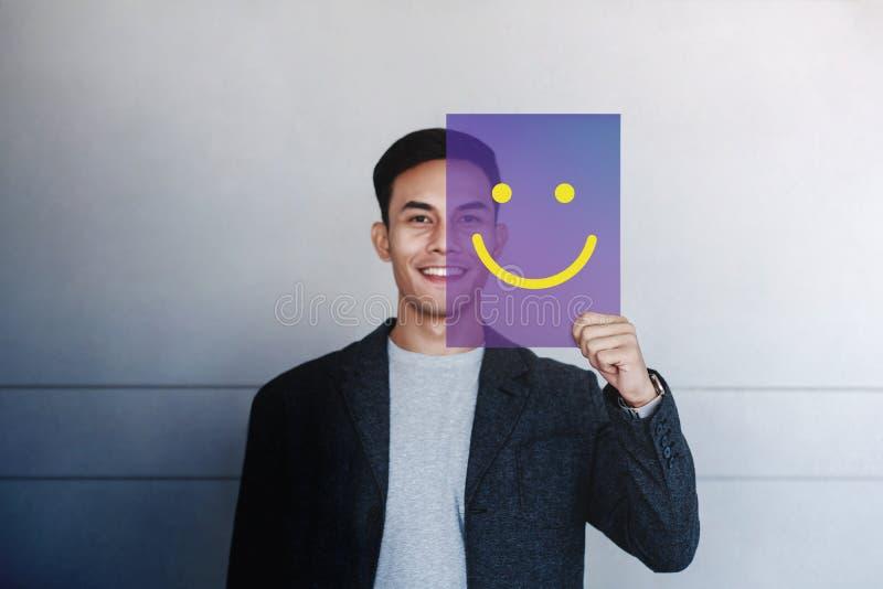 愉快的人概念 年轻人在透明卡片的微笑和展示微笑象 正面人面表示 免版税库存照片
