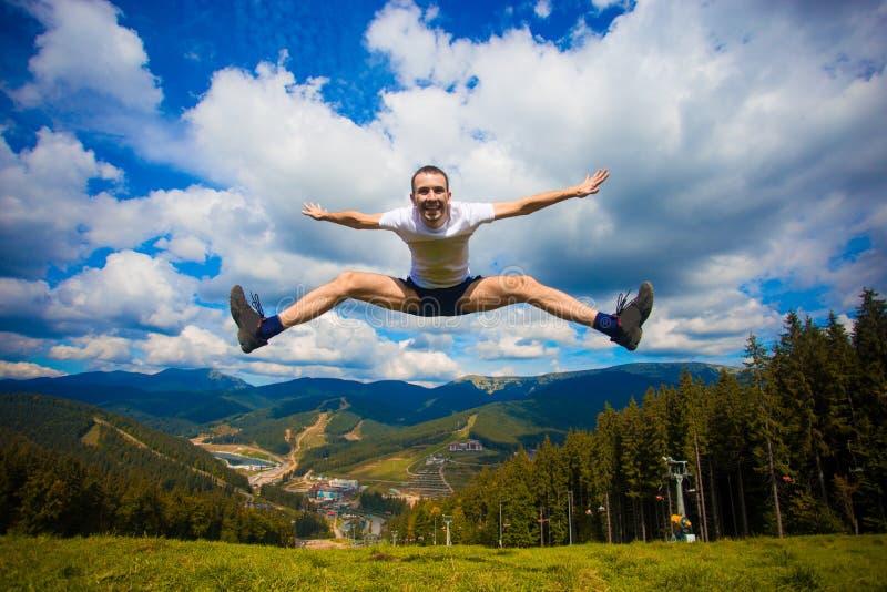 愉快的人获得乐趣在小山,在背景的山顶部 库存图片
