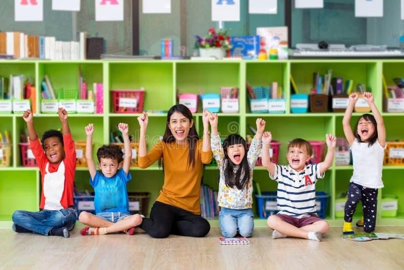 愉快的亚裔女老师和混合的族种孩子在教室,幼儿园前学校概念 免版税库存图片