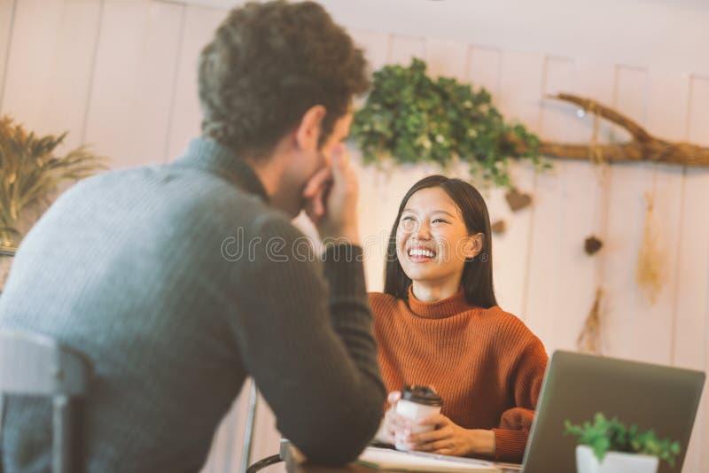 愉快的亚裔聊天和使用膝上型计算机的女孩和朋友在咖啡馆在咖啡馆咖啡馆在笑的大学一起谈话和 免版税库存图片