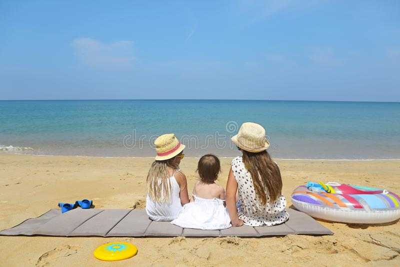 愉快的使用在一个美丽的海滩的沙子的女婴和她的姐妹 免版税图库摄影