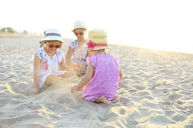 愉快的使用在一个美丽的海滩的沙子的女婴和她的姐妹 库存照片