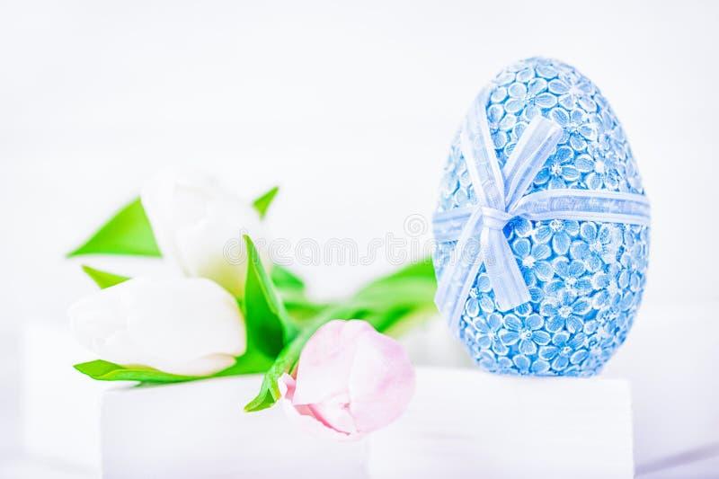 愉快的复活节 复活节蓝色鸡蛋和白色和桃红色郁金香在白色背景 库存图片