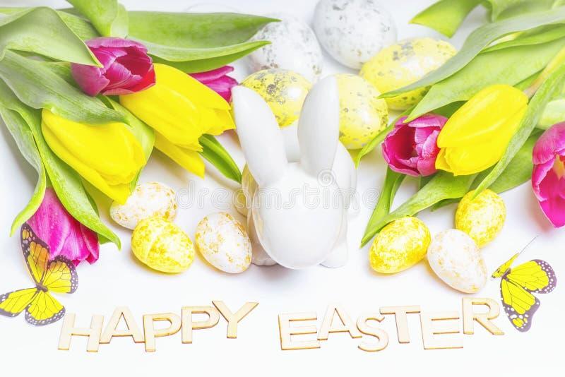 愉快的复活节 在白色背景的复活节白色兔宝宝用复活节彩蛋和新鲜的郁金香 复活节与复活节兔子的贺卡 库存照片
