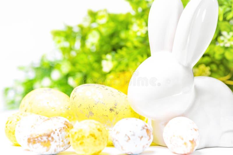 愉快的复活节 在白色背景的复活节白色兔宝宝用复活节彩蛋 复活节与复活节兔子的贺卡 免版税库存图片