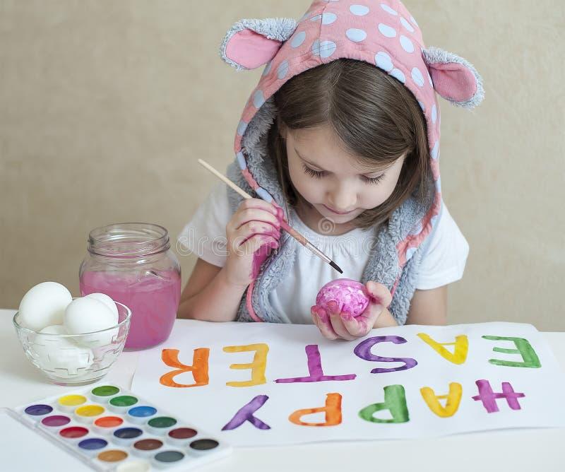 愉快的复活节 桃红色兔宝宝耳朵的女孩画家用五颜六色的被绘的鸡蛋 孩子为复活节做准备 手画 库存图片