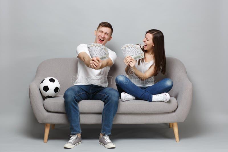愉快的夫妇妇女人足球迷在美元钞票使支持喜爱的队振作,拿着金钱爱好者,现金 库存图片