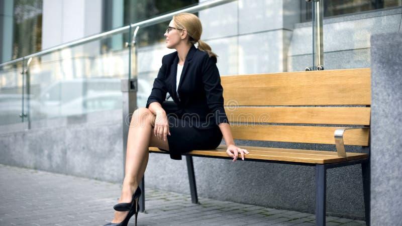 愉快的女实业家坐长凳,满意对成功的工作日,休息 库存照片