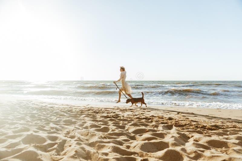 愉快的妇女的图象草帽的,跑与她的棕色狗沿海 免版税库存照片