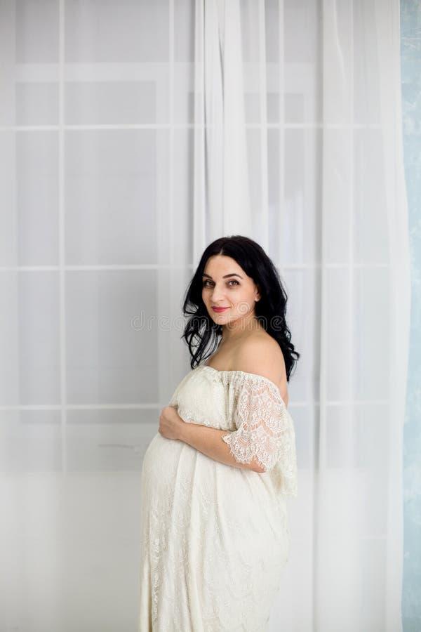 愉快的孕妇时尚画象白色礼服的 库存图片