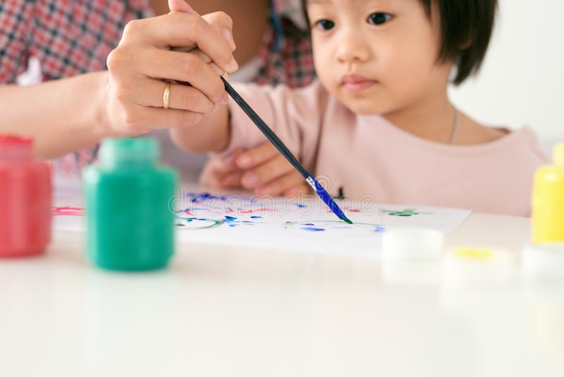 愉快的家庭母亲和女儿一起绘 亚裔妇女帮助她的儿童女孩 免版税库存照片