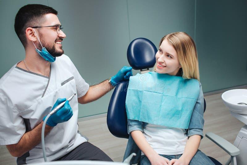 愉快的年轻女性客户在椅子在牙科方面坐 她看牙医和微笑 面具和白色抢夺的年轻人 免版税库存照片