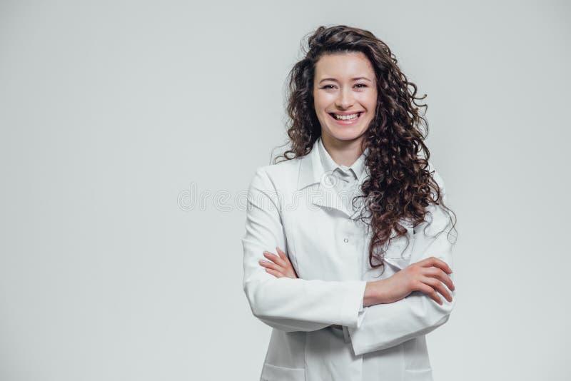 愉快的年轻微笑的女孩医生画象  穿戴在一件白色长袍 站立用在灰色的横渡的手 库存照片