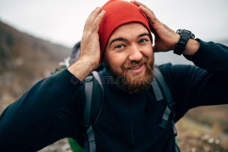 愉快的徒步旅行者年轻人接近的画象红色帽子的,远足在山 微笑在迁徙期间的旅客有胡子的男性 免版税库存图片