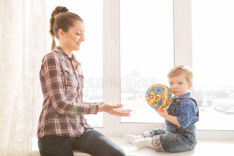 愉快的在家打五颜六色的球的母亲和她的婴孩 库存图片