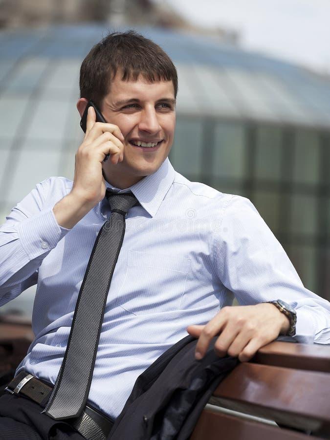 愉快的典雅的商人由室外的电话讲话 库存图片