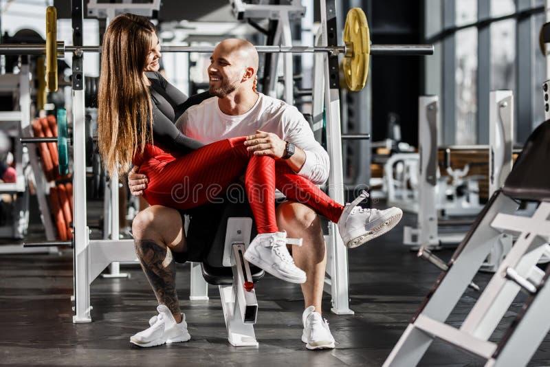 愉快的浪漫运动夫妇 苗条美女坐膝盖坚强的运动人和拥抱在 库存照片