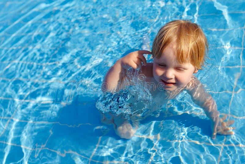 愉快的矮小的公平的儿童男孩在游泳场的水中 免版税库存照片