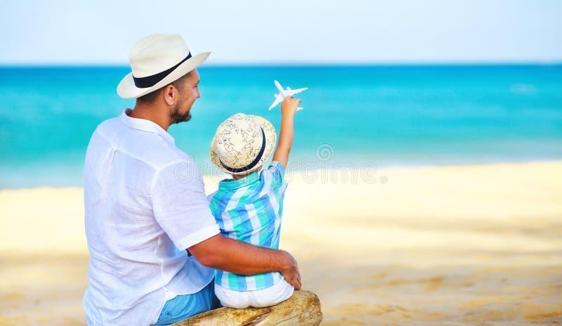 愉快的父亲节!海滩的爸爸和儿童儿子由有式样玩具飞机的海 免版税库存图片
