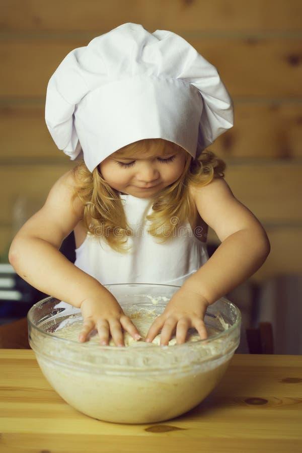 愉快的男孩儿童厨师揉的面团 库存图片