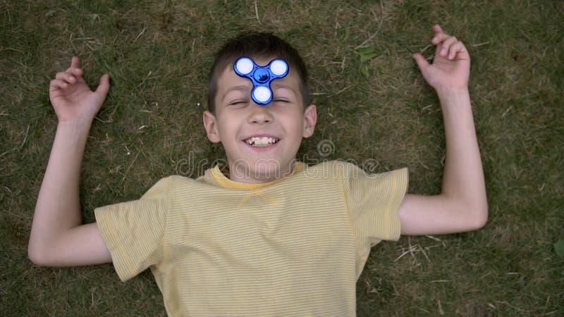 愉快的男孩扭转鼻子的在草户外的锭床工人和谎言 免版税库存照片
