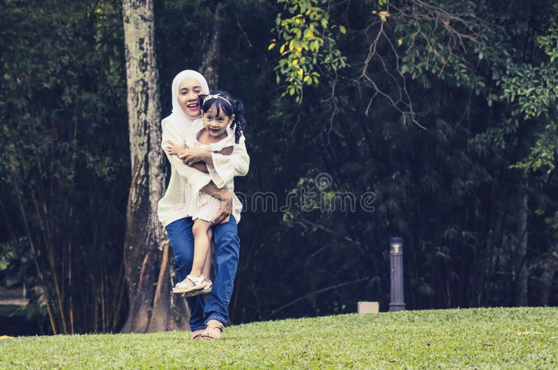 愉快的表示年轻母亲享用与她的女儿,获得乐趣在公园 库存照片