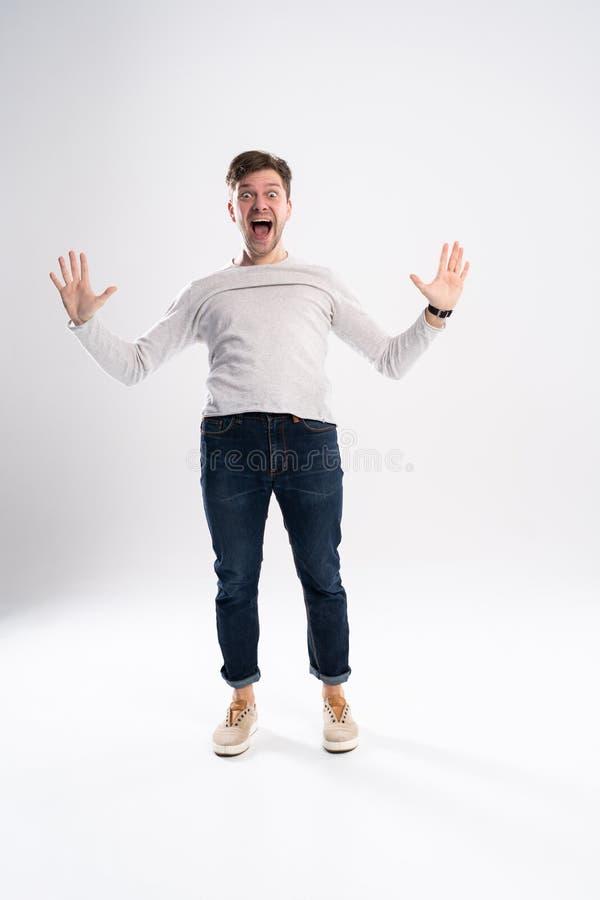 愉快的赢利地区 打手势和保持嘴的愉快的年轻帅哥全长画象开放,当站立反对时 库存照片