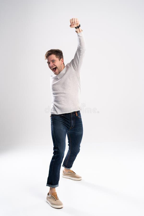愉快的赢利地区 打手势和保持嘴的愉快的年轻帅哥全长画象开放,当站立反对时 免版税图库摄影