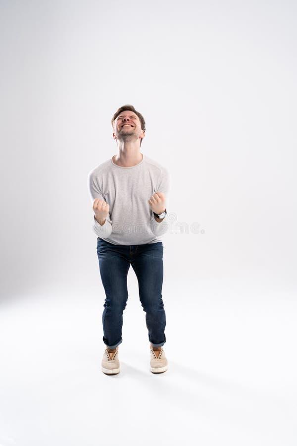 愉快的赢利地区 打手势和保持嘴的愉快的年轻帅哥全长画象开放,当站立反对时 免版税库存图片