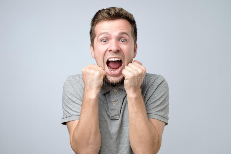 愉快的赢利地区 打手势和保留嘴的愉快的年轻帅哥打开了 免版税库存图片